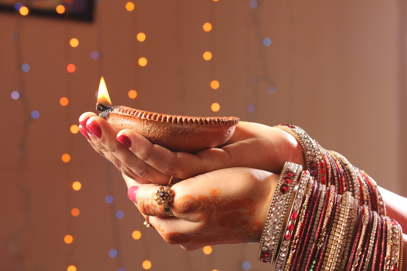 Hands holding a candle for Diwali